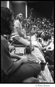 Thumbnail of Ram Dass on stage during an appearance at the College of Marin Krishna Das in the foreground