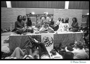 Thumbnail of Ram Dass and associates on stage during an appearance at the College of Marin Krishna Das (left) and Cathy Brown (Usha, right) flanking the stage