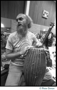 Thumbnail of Ram Dass playing drums during an appearance at the College of Marin