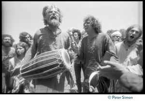Thumbnail of Bhagavan Das drumming on the lawn during Ram Dass's appearance at Sonoma State       University, Peter Simon recording his singing