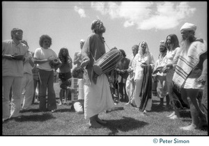 Thumbnail of Bhagavan Das playing a drum and singing with members of the Ram Dass satsang during Ram Dass's appearance at Sonoma State       University