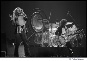 Thumbnail of Robert Plant (vocals), on stage with John Bonham (drums) and Jimmy Page (guitar) in             concert with Led Zeppelin at the Forum in Inglewood