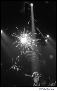 Thumbnail of Robert Plant (vocals), on stage, with fireworks superimposed,  in concert with Led Zeppelin at the Forum in Inglewood