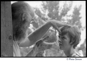 Thumbnail of Ram Dass laying on hands on a woman, Rowe Center spiritual retreat