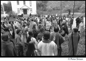 Thumbnail of Ram Dass speaking to attendees wrapped in blankets, Rowe Center spiritual retreat Rowe Town Hall building in the background