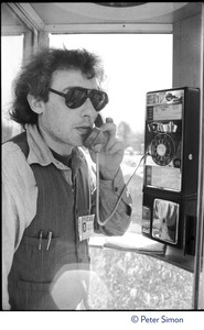 Thumbnail of Charles Light (wearing a press pass for Green Mountain Post Films) using a pay phone