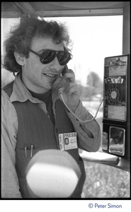 Thumbnail of Charles Light (wearing press pass for Green Mountain Post Films) using a pay phone