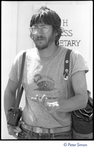 Thumbnail of Harvey Wasserman in a Clamshell Alliance t-shirt, with camera and bag, occupation of Seabrook Nuclear Power Plant