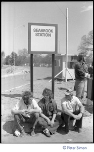 Thumbnail of Occupiers seated beneath sign for Seabrook Station, as the occupation             of Seabrook Nuclear Power Plant gets under way