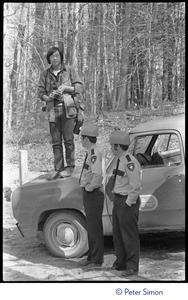 Thumbnail of Photographer stands on the hood of a patrol car as Power Plant security guards             look on, during the early stages of the occupation of the Seabrook Nuclear Power Plant