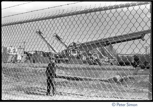 Thumbnail of Security guard and power plant seen through a chain link fence, Seabrook Nuclear             Power Plant