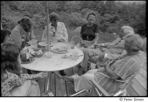 Thumbnail of Ram Dass and dad at mum's: Ram Dass, Phyllis Alpert, Andrea Simon, George Alpert, unidentified, Ronni Simon, and unidentified, clockwise from top left, seated on a patio