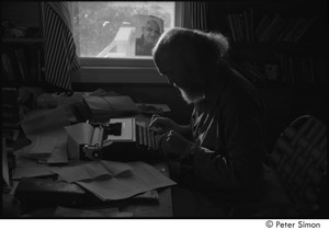 Thumbnail of Ram Dass at typewriter: Ram Dass typing, with a portrait of Neem Karoli Baba in the background