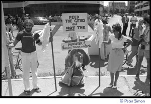 Thumbnail of Protesters associated with Mobilization for Survival at an antinuclear             demonstration near Draper Laboratory, MIT, carrying a sign reading 'Feed the cities and             not the monster of nuclear power and arms'