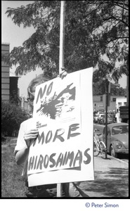 Thumbnail of Protester at a Mobilization for Survival antinuclear demonstration near Draper             Laboratory, MIT, with sign reading 'Fund human needs: No more Hiroshimas'