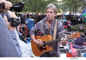 Thumbnail of Occupy Wall Street: man playing guitar and singing in front of video camera