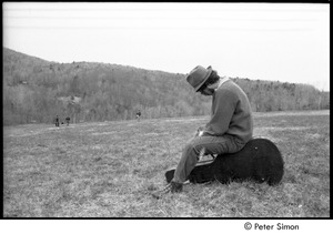 Thumbnail of May Day at Packer Corners commune: man in a field, sitting on a guitar case