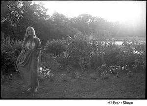 Thumbnail of 'Nel' standing by flowers and pond