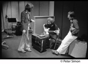 Thumbnail of Grateful Dead in the studio (Automated Sound) Right to left: Keith Olsen (producer, seated on amplifier), Jerry Garcia (seated, paying guitar), Bob Weir