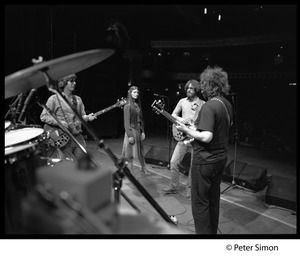 Thumbnail of Grateful Dead rehearsing on stage Right to left: Jerry Garcia, Bob Weir, Donna Jean Godchaux, and Phil Lesh