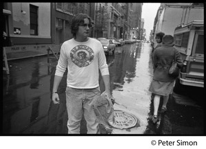 Thumbnail of Crew member(?) in Grateful Dead shirt on rain soaked streets