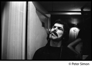 Thumbnail of Mickey Hart, smoking a cigarette, standing by the crew room door