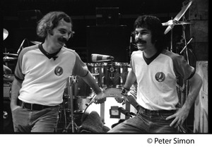 Thumbnail of Bill Kreutzman (left) and Mickey Hart, drummers for the Grateful Dead, standing             in front of their kit
