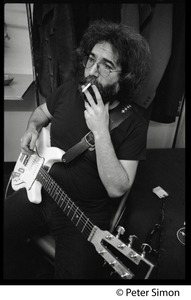 Thumbnail of Jerry Garcia: half-length portrait with guitar, smoking a cigarette
