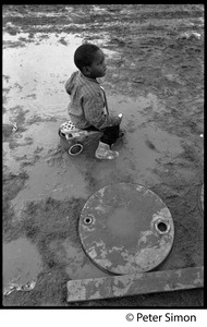 Thumbnail of Young boy riding a toy car in the mud, Resurrection City