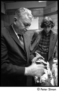 Thumbnail of Stephen Davis watches as narcotics officer Duncan MacNeil unwraps a tinfoil-wrapped package of drugs
