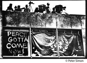Thumbnail of Press covering a demonstration from rooftop, window below them draped with a             United Nations flag and painted slogan 'Peace gotta come now' (solarized)