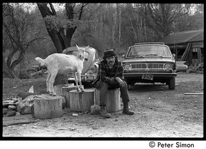 Thumbnail of Michael Gies, seated on a stump next to a goat, Packer Corners commune