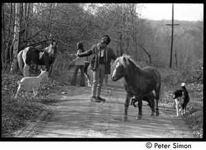 Thumbnail of Elliot Blinder and Nancy Hazen on a dirt road with farm animals, Tree Frog Farm             commune Blinder, facing the camera, spreads his arms