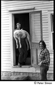 Thumbnail of Steve Marsden holding a goat, standing in a doorway, with Verandah Porche, Packer Corners commune