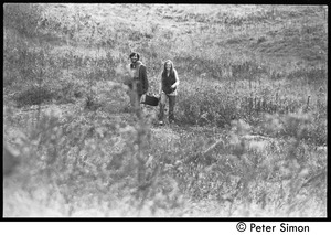 Thumbnail of Elliot Blinder and Nancy Hazen walking through a field, Tree Frog Farm             commune