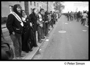 Thumbnail of Protesters lining the street, one wearing a 'marshal' sash: Vietnam Moratorium march on Washington