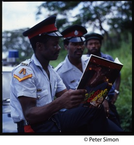 Thumbnail of Jamaican police reading a copy of Reggae International, by Neville Hinds