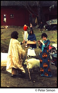 Thumbnail of Elliot Blinder, Casey the goat, with Jenny Buell playing the flute in the farmyard, Tree Frog Farm             commune Catherine Blinder approaching in the background