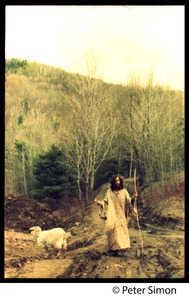 Thumbnail of Elliot Blinder on a dirt road near Tree Frog Farm commune with Casey the goat on         leash