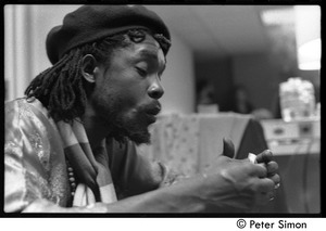 Thumbnail of Peter Tosh rolling a marijuana cigarette backstage during his appearance on Saturday Night Live