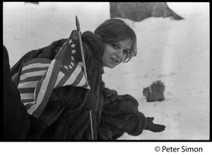 Thumbnail of Women with an American flag (with circular field of stars), leaning down in the             snow: Resistance antiwar rally
