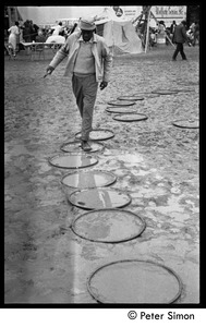 Thumbnail of Man walking across muddy ground, using oil drum lids as stepping stones, Resurrection City encampment