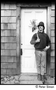 Thumbnail of Elliot Blinder wearing an old police helmet and standing at the house door,             holding a spatula, Packer Corners commune