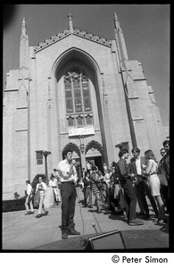 Thumbnail of Sanctuary movement and occupation of Marsh Chapel A speaker with a portable PA system addresses supporters in front of the             Chapel; a banner hangs over the entrance reading 'Sanctuary'