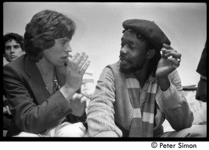 Thumbnail of Mick Jagger and Peter Tosh sharing a marijuana cigarette backstage during an appearance on Saturday Night Live