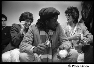 Thumbnail of Peter Tosh backstage during an appearance on Saturday Night Live, relaxing with             Mick Jagger and Keith Richards
