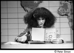 Thumbnail of Gilder Radner as Roseann Roseannadanna on Weekend Update set, Saturday Night Live