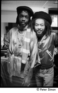Thumbnail of Peter Tosh (left) with unidentified man backstage on Saturday Night Live:             three-quarter length portrait