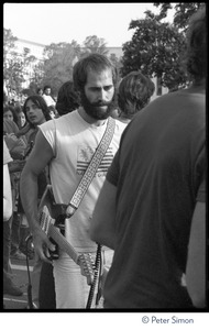 Thumbnail of John Hall, with guitar, heading to the stage at the No Nukes concert and protest, Washington, D.C. Jackson Browne is visible in the background