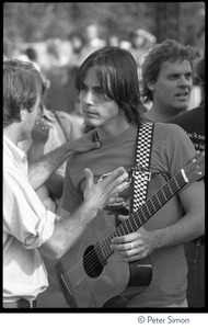 Thumbnail of Jackson Browne, with acoustic guitar, talking to unidentified man at the No Nukes concert and protest, Washington, D.C.